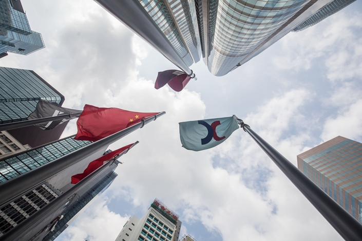 The corporate flag for Hong Kong Exchanges & Clearing Ltd., right, and the Chinese flag, left, fly outside the Exchange Square complex in Hong Kong on Sept. 16, 2019. Photo: Bloomberg