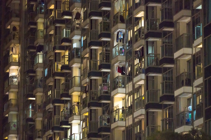 Residential buildings stand illuminated at night in Hong Kong on Feb. 20. Photographer: Bloomberg