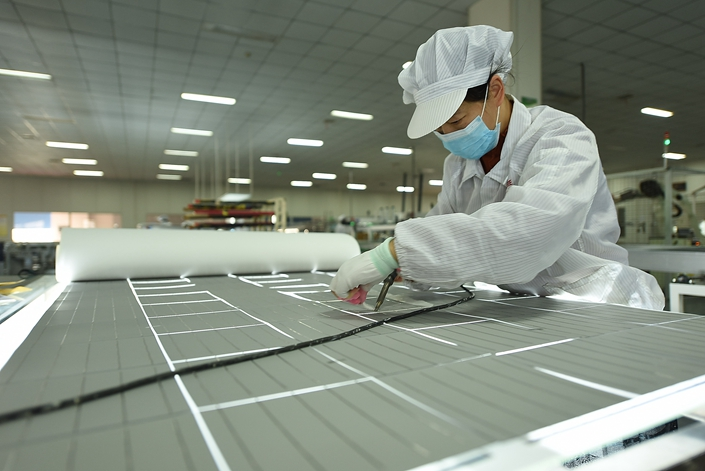Workers produce solar photovoltaic cells at a workshop in East China's Jiangsu province, March 21. Photo: IC Photo
