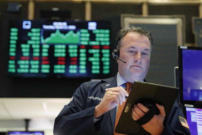 A trader works on the floor of the New York Stock Exchange shortly before the closing bell on March 17.
