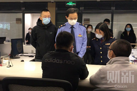 Photo: Zhan Ketuan, co-founder of Bitmain Technologies (front right) waits to receive a new business registration license at the Beijing Haidian District Government Service Center. Photo: Hu Yue/Caixin