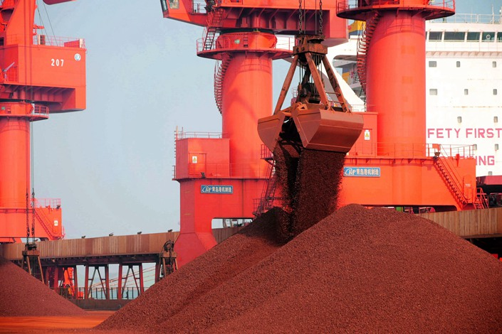 Iron ore gets unloaded from a cargo ship on Jan. 20 at a port in Qingdao, East China's Shandong province.