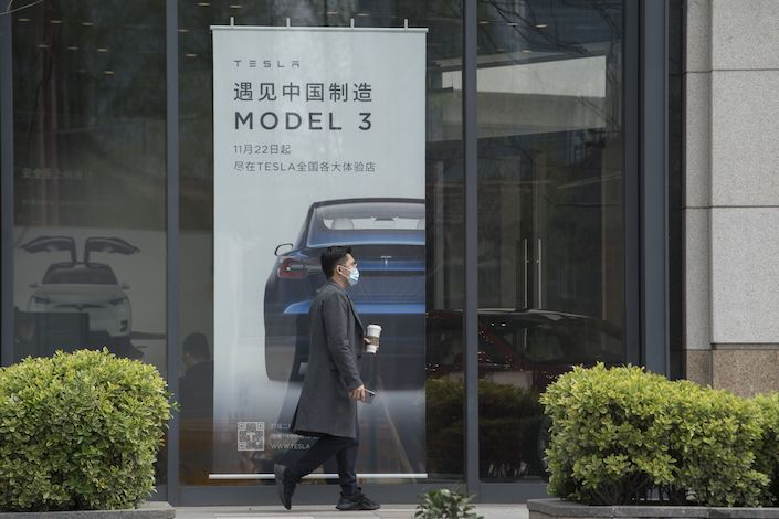 A pedestrian walks past a Tesla Inc. dealership in Shanghai. Photo: Bloomberg