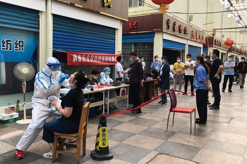 Residents wait in line for Covid-19 nucleic acid tests May 15 in Wuhan. Photo: Zeng Yukun/Caixin
