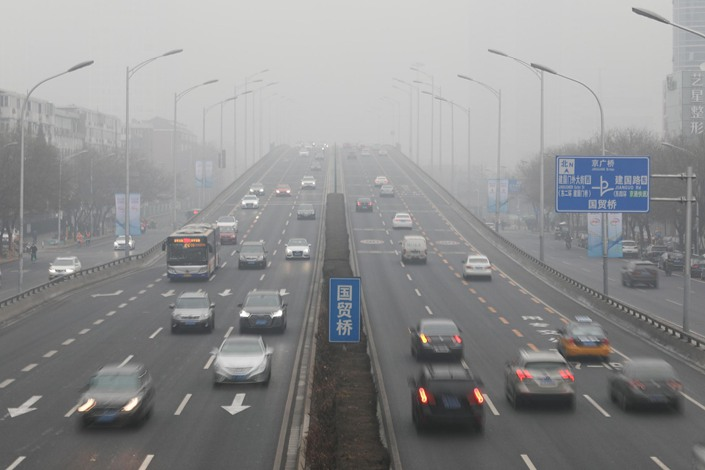 Cars drive through Beijing's heavy pollution on Feb. 13.