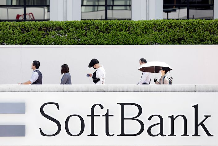 Pedestrians wearing protective masks walk past signage for SoftBank Corp. near a store in Tokyo. Photo: Bloomberg