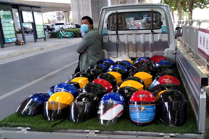 A hawker sells helmets out of the back of a truck on Tuesday in Zhengzhou, North China's Henan province.