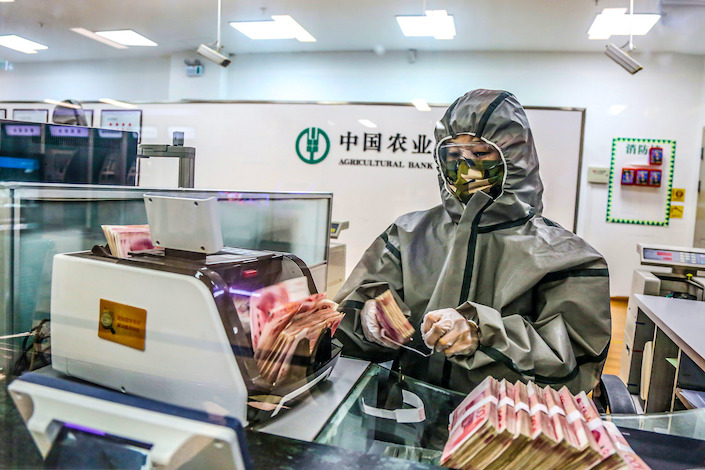 A teller wearing protective gear March 7, 2020, at a branch of Agriculture Bank of China in Harbin.