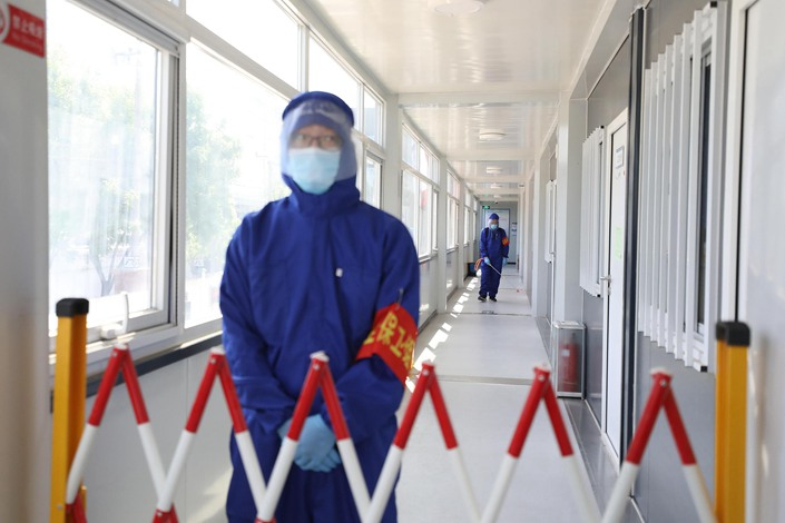 Workers disinfect an area in a remote part of Beijing on Tuesday,