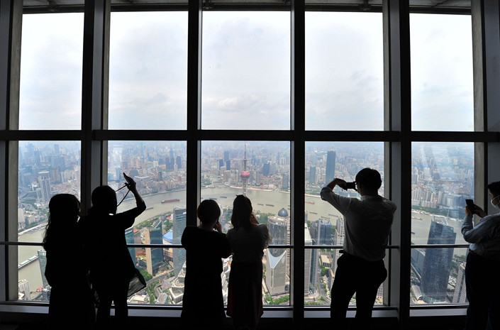 Tourists take photos from the heights of the Shanghai World Financial Center in Shanghai on May 15.