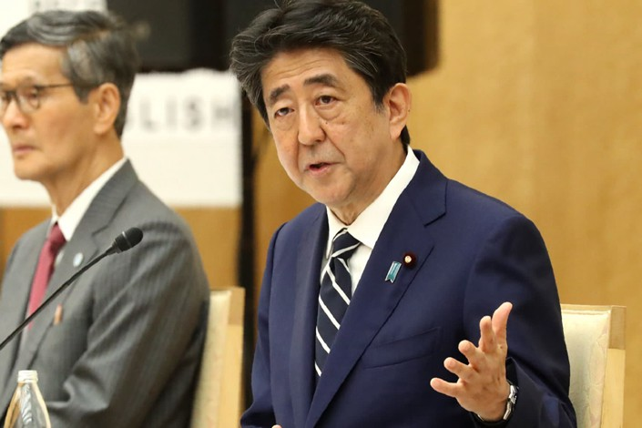 Prime Minister Shinzo Abe speaks at a May 25 meeting of his government's coronavirus advisory panel with member Shigeru Omi, left, a former World Health Organization official. Photo: Nikkei Asian Review