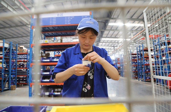 Workers inspect the quality of products Thursday at an equipment manufacturing workshop in Pingdingshan, Henan province.