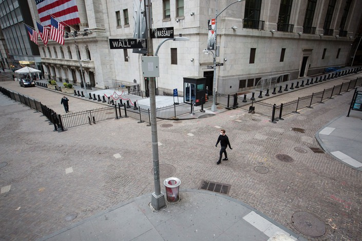 A pedestrian wearing a protective mask walks along Wall Street in New York on March 30. Photo: Bloomberg