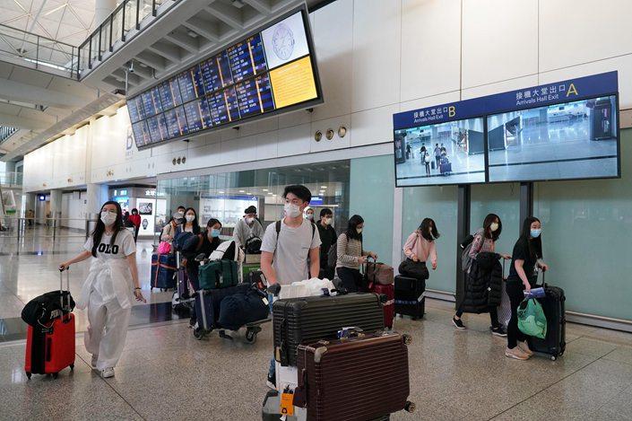 Passengers arrive at Hong Kong International Airport on March 18.