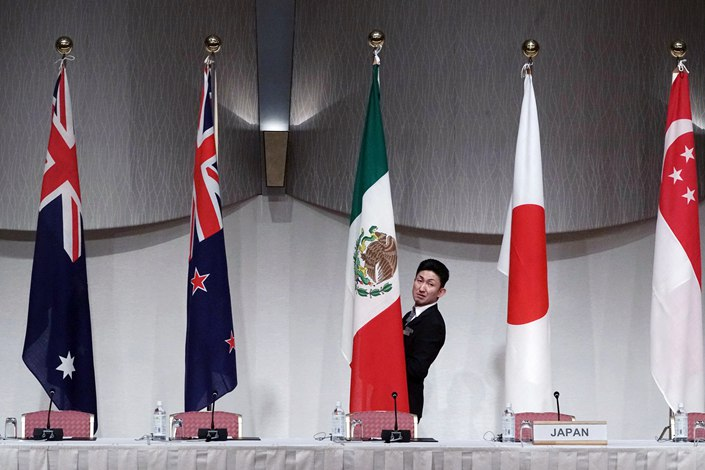 A staff member adjusts the Mexican flag before a joint press conference of the Comprehensive and Progressive Trans-Pacific Partnership (CPTPP) in Tokyo in January 2019.