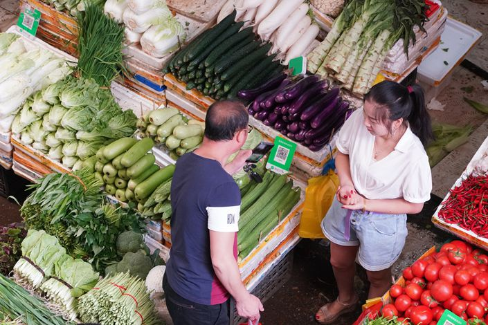 A shopper scans a WeChat payment code at a vegetable market in Huaihua, Central China's Hunan Province.