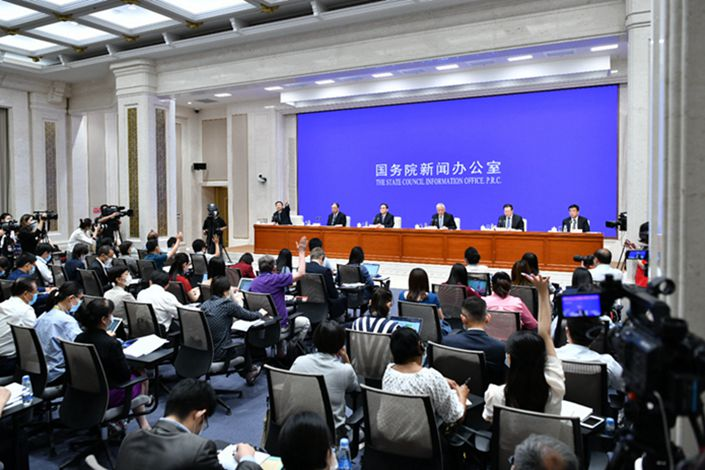 Reports raise their hands to ask questions at a State Council press conference Sunday. Photo: Xinhua