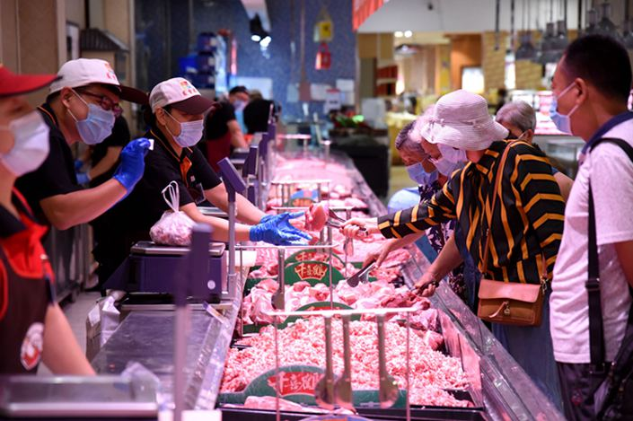 Customers buy meat at a supermarket in the city of Handan in Hebei province