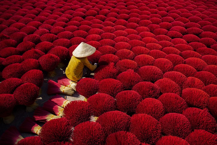 A worker sits surrounded by thousands of incense sticks in Quang Phu Cau, a village in Hanoi, Vietnam, where the sticks have been traditionally made for hundreds of years.