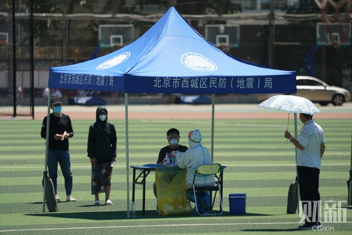 A resident receives a nucleic acid test at Guangan Stadium in Beijing's Xicheng district Sunday. Photo: Cai Yingli/Caixin