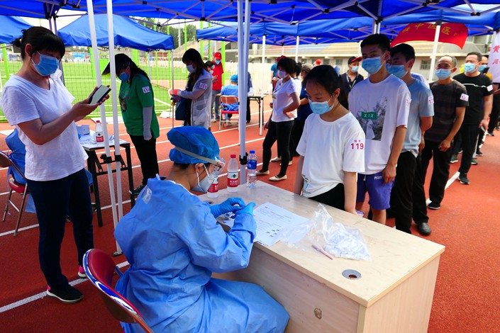 Residents line up for nucleic acid tests at a sports center in Beijing, June 17.