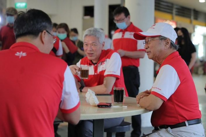 Lee Hsien Yang (center) and Progress Singapore Party chief Dr. Tan Cheng Bock sit together Wednesday at a market in Singapore. Photo: The Straits Times