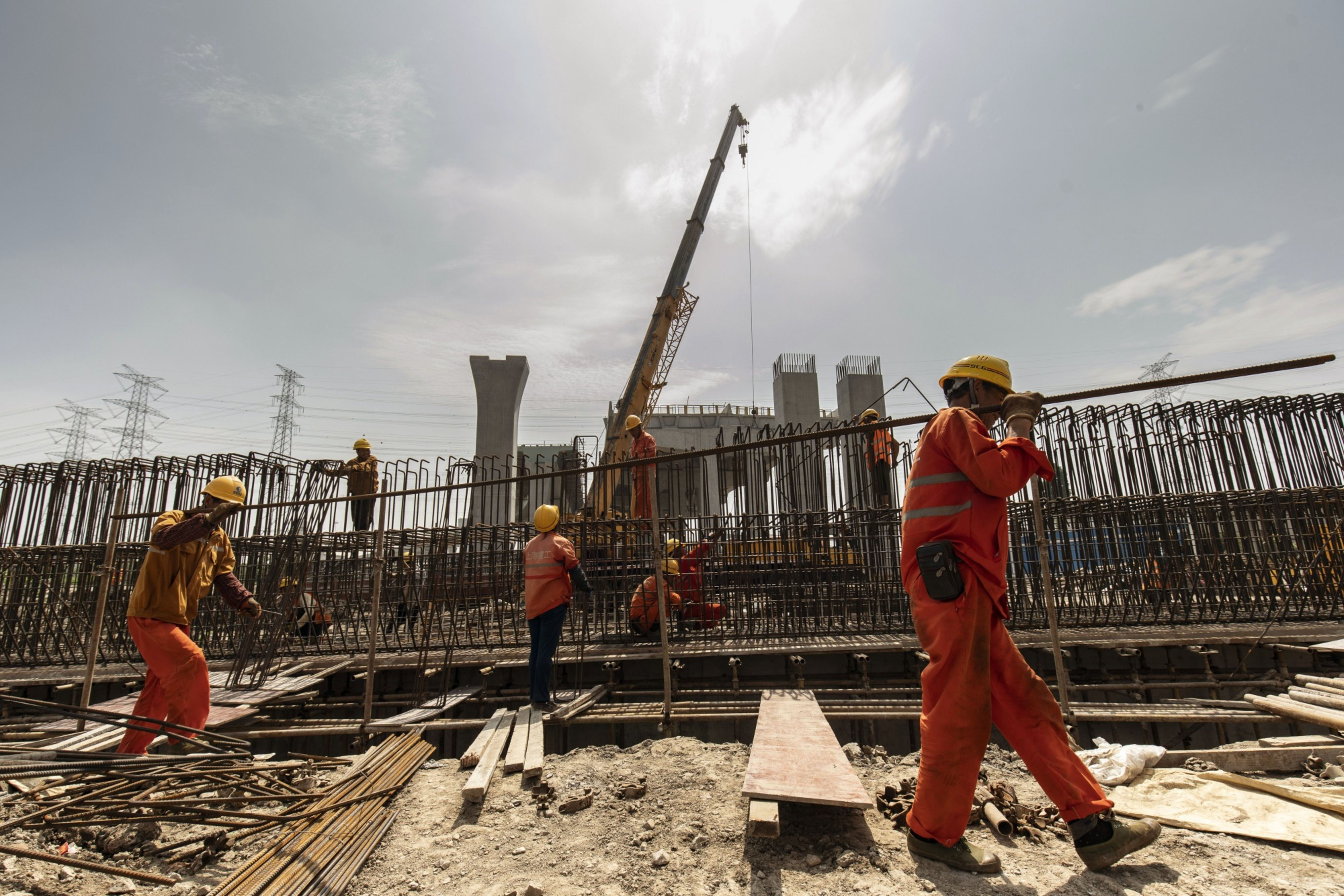 Workers carry a steel bar at the construction site on the outskirts of Shanghai on June 12. Photo: Bloomberg