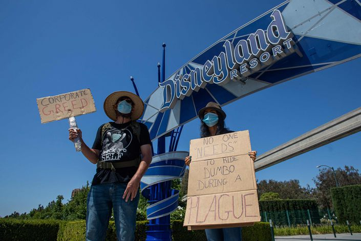 People hold signs in front of Disneyland Resort in Anaheim, California, on June 27 calling for higher safety standards before its reopening on July 17.
