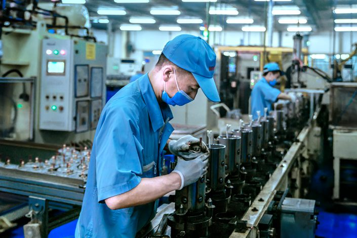 A worker makes air conditioning equipment at a factory in Mianyang, Sichuan province, on June 5.