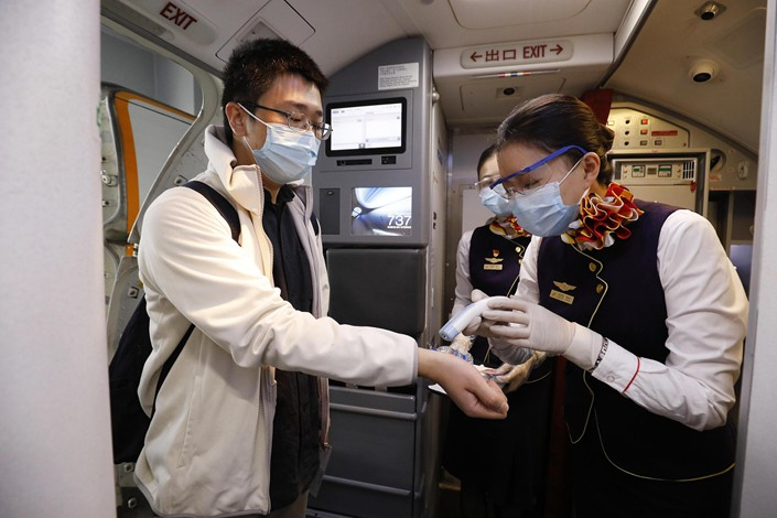 A flight attendant takes the temperature of a passenger in an airplane in Shanghai on April 13.