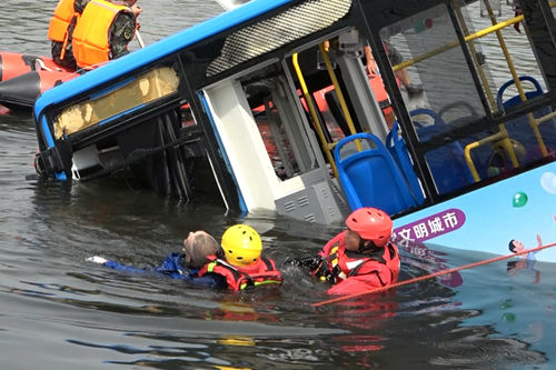 Rescue staff pull a victim out of the bus that sank into Hongshan Lake reservoir.
