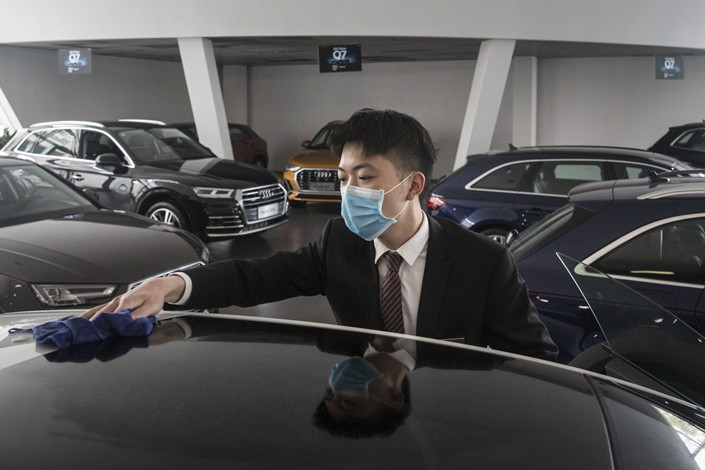 An employee wearing a protective mask wipes a vehicle on display inside an Audi AG dealership in Wuhan, Hubei province, on April 6. Photo: Bloomberg