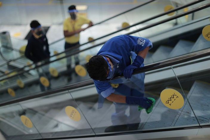 A janitor wipes down an escalator Wednesday in a recently reopened shopping mall in Mexico City.