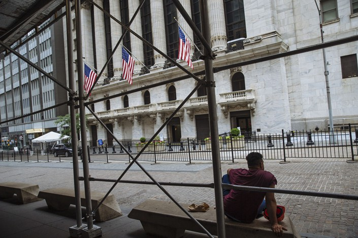 A person sits on a bench outside the New York Stock Exchange (NYSE) in New York, U.S., on Wednesday, June 24, 2020. Photo: Bloomberg