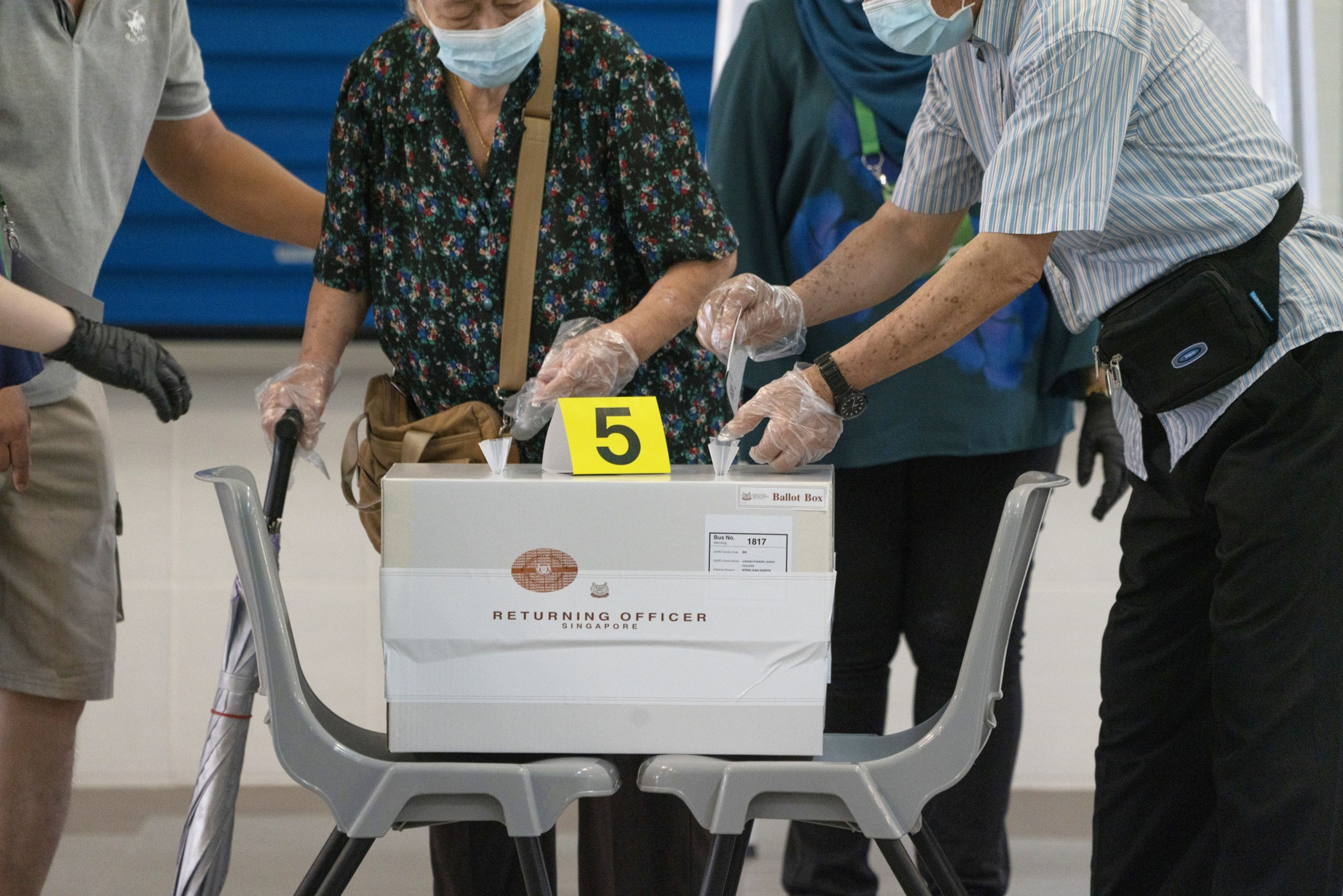 A voter wearing a protective mask and gloves is assisted to place her vote slip into a ballot box during the Early and Senior Voting Band at the Dunearn Secondary School polling station in Singapore. Photo: Bloomberg