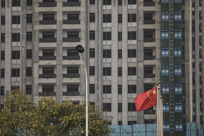 A Chinese flag flies in front of an unfinished building complex in Haikou, South China's Hainan province, in March 2018. Photo: Bloomberg