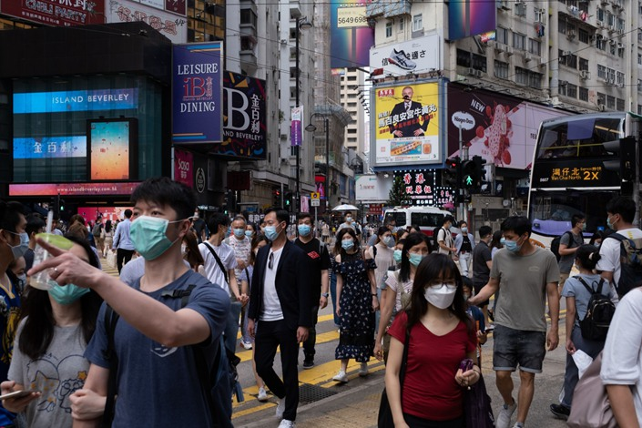 Pedestrians wearing protective masks in the Causeway Bay district in Hong Kong
