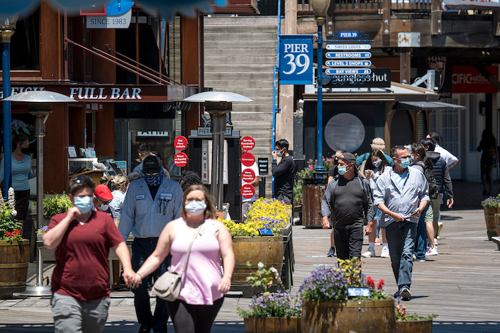 People wearing protective masks walk on Pier 39 in San Francisco, California, on June 22, 2020.