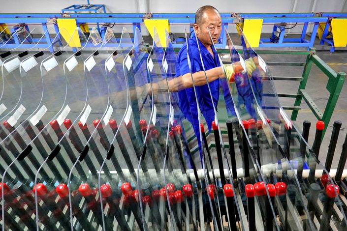 A worker works on a production line Friday at an auto glass manufacturer in Weihai, East China's Shandong province.