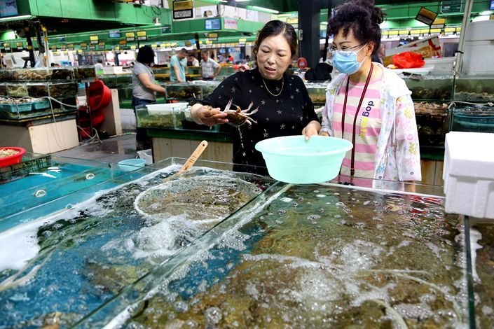 Consumers buy fresh seafood on July 9 at a market in Lianyungang, East China's Jiangsu Province.