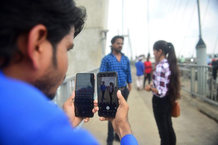 Indian mobile users browse through the Chinese owned video-sharing app TikTok in Amritsar on June 30.