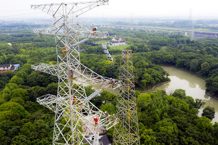 Workers install a power supply device on June 24 in Taicang, Jiangsu province.