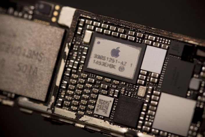 The Apple Inc. logo is seen on the power management supply integrated circuit (IC) chip mounted in the logic board of an iPhone 6 smartphone in an arranged photograph in Bangkok, Thailand, on Saturday, Feb. 3, 2018. Photo: Bloomberg