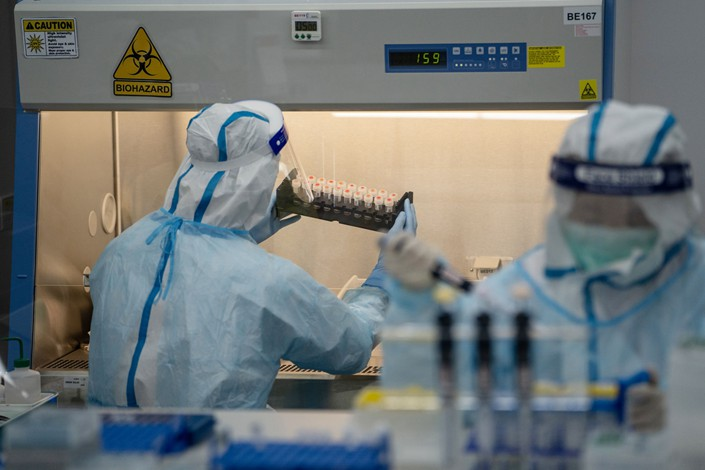 A lab technician handles saliva samples for Covid-19 testing at Prenetics' laboratory in Hong Kong on July 31. Photo: Bloomberg