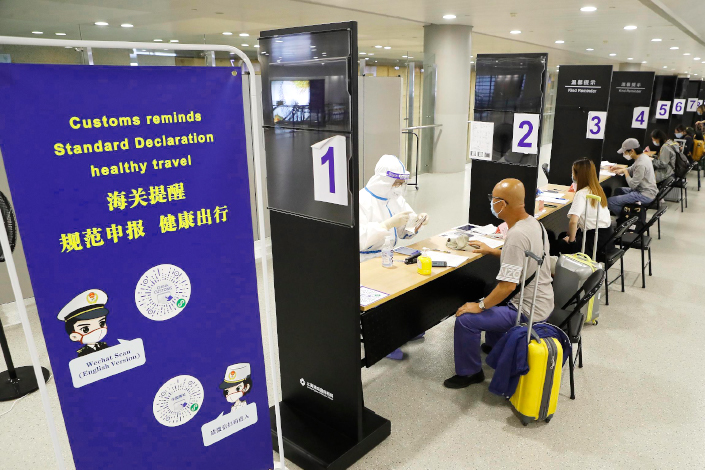 Customs officers check inbound passengers' health information on July 31 at Shanghai Pudong International Airport.