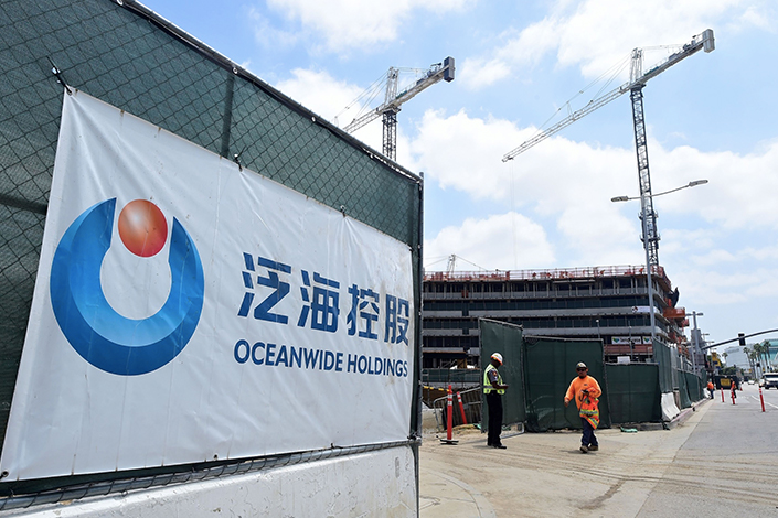 A banner of China's Oceanwide Real Estate Group is displayed at the construction site of a property, purchased in 2014, located across the steet from the Staples Center in Los Angeles, California on May 17, 2016.  Photo: Bloomberg