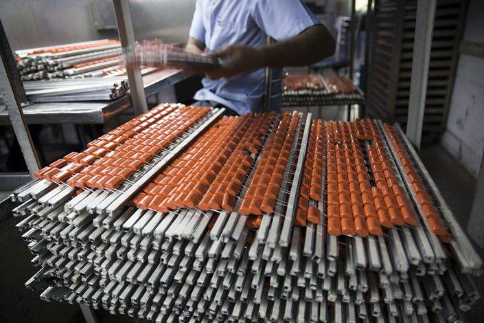 An employee handles capacitors at the Deki Electronics Ltd. factory in Noida, Uttar Pradesh, India, on Feb. 11.