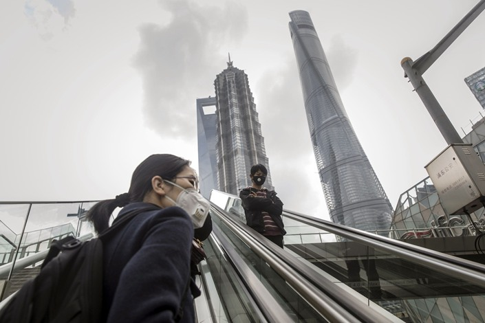 Pedestrians wearing protective masks ride an escalator in the Lujiazui Financial District of Shanghai on March 2. Photo: Bloomberg