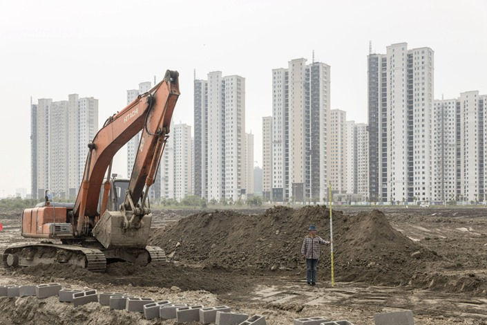 A worker stands with a level staff next to an excavator on April 26 at a construction site for a school in Ningbo, East China's Zhejiang province. Photo: Bloomberg