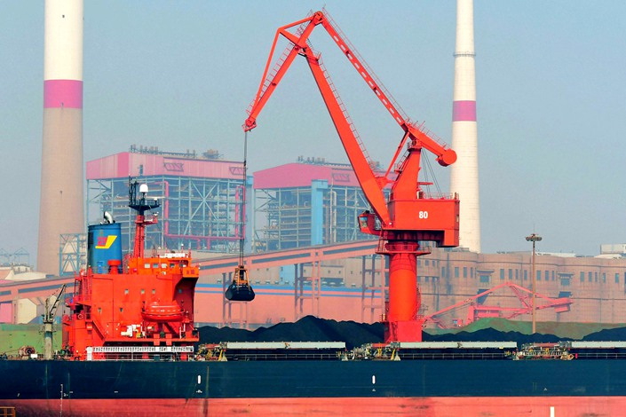 A cargo ship unloads imported iron ore at the Qingdao port ore terminal in East China's Shandong province on April 3.